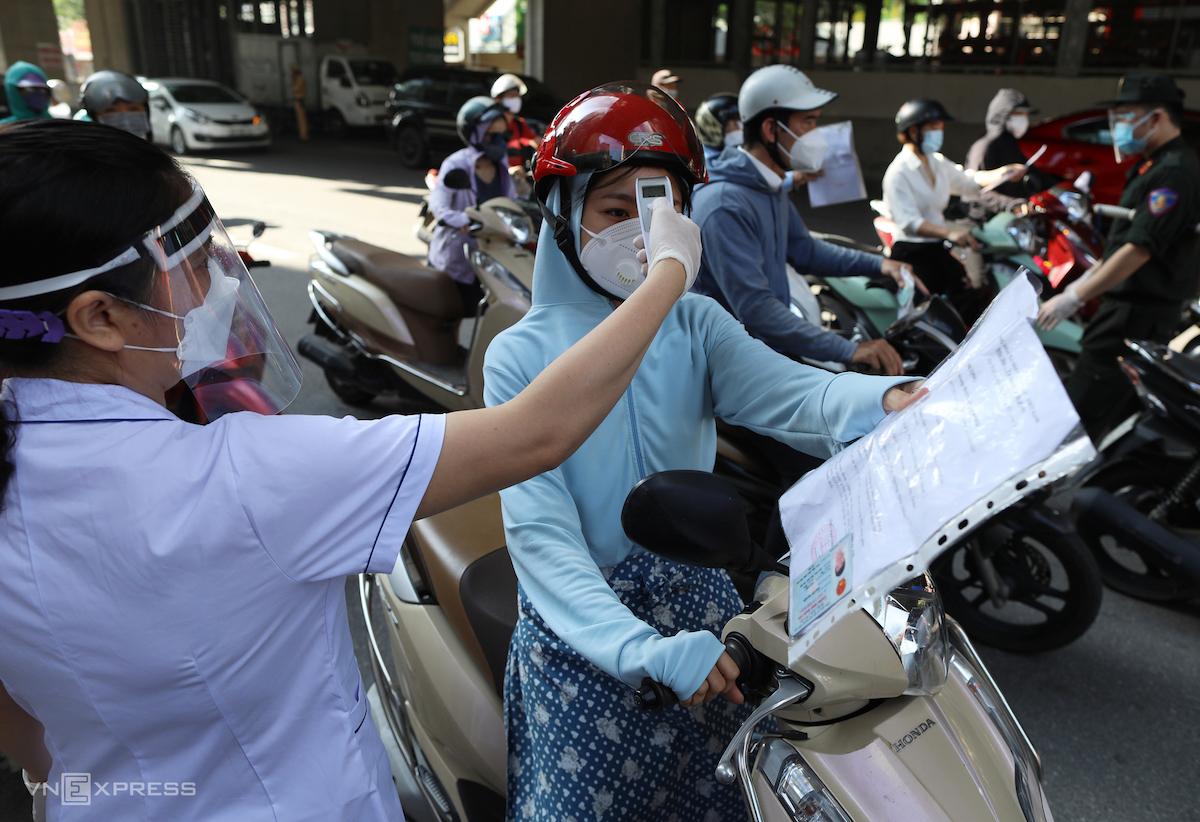 Lực lượng chức năng tại chốt kiểm dịch trên đường Hồ Tùng Mậu làm việc không ngơi tay. Người dân được đo thân nhiệt trước khi kiểm tra giấy đi đường. Ảnh: Ngọc Thành