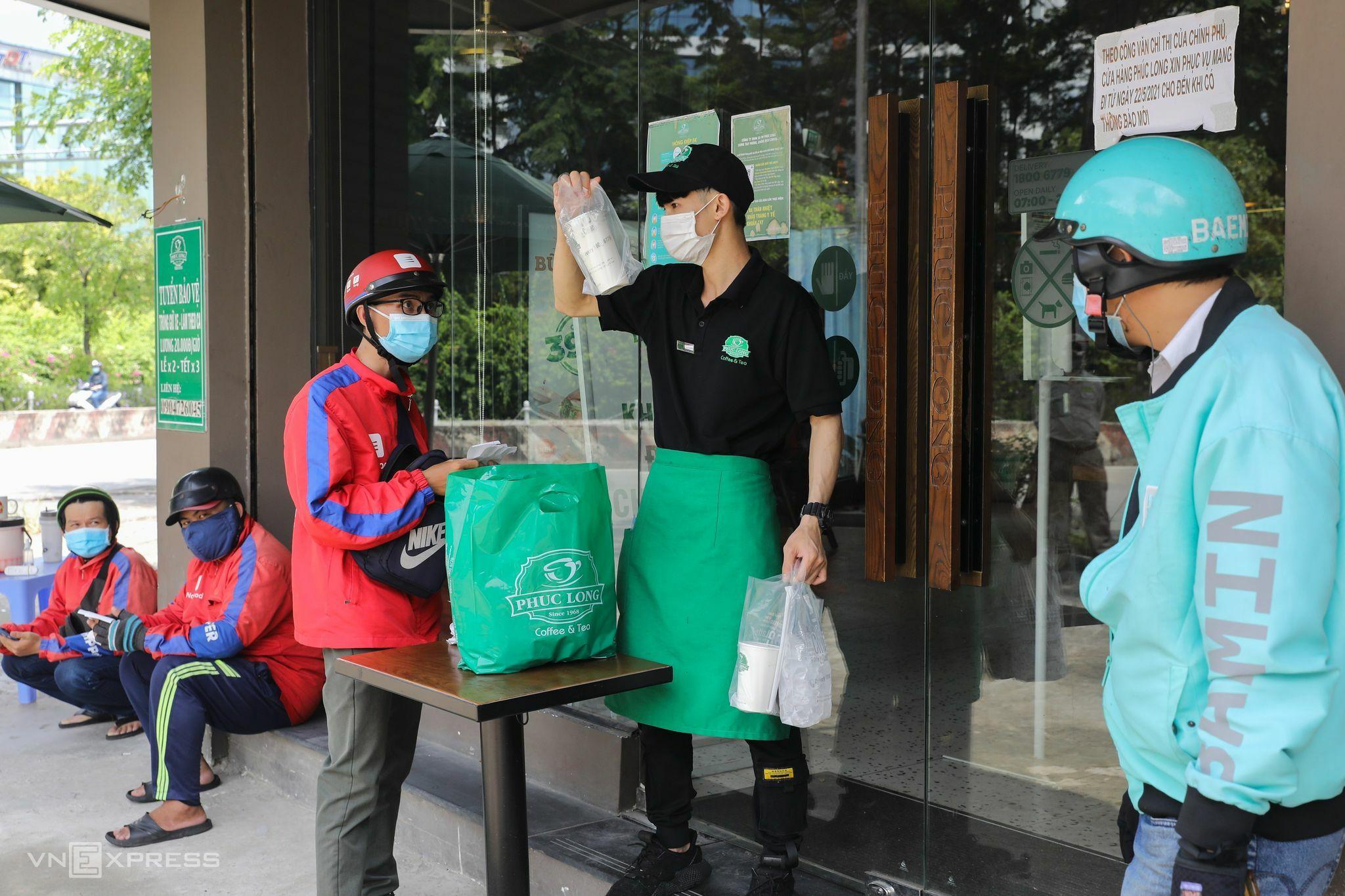 Shipper chờ nhận hàng tại một tiệm cà phê trên đường Nguyễn Hữu Thọ, quận 7 ngày 16/9. Ảnh: Quỳnh Trần