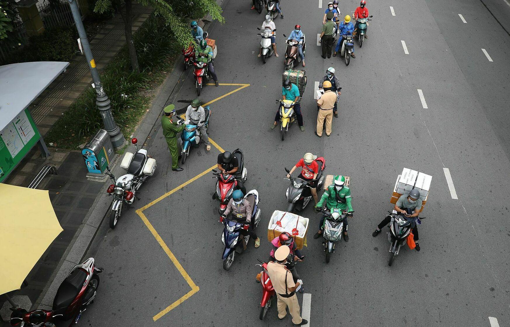 Một số tài xế giao hàng tại chốt kiểm soát trên đường Hoàng Văn Thụ, quận Tân Bình, TP HCM ngày 15/8. Ảnh: Quỳnh Trần