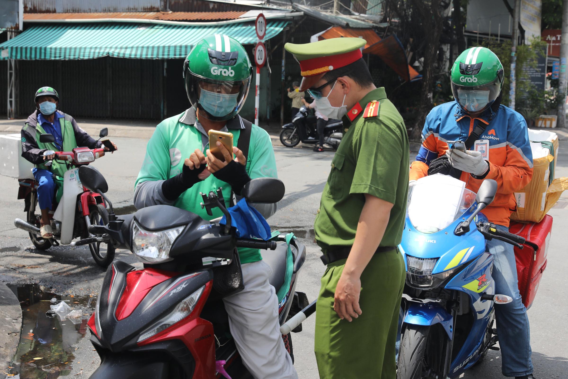 Cán bộ trực chốt đang kiểm tra shipper hoạt động tại quận 7, ngày 16/9. Ảnh: Quỳnh Trần