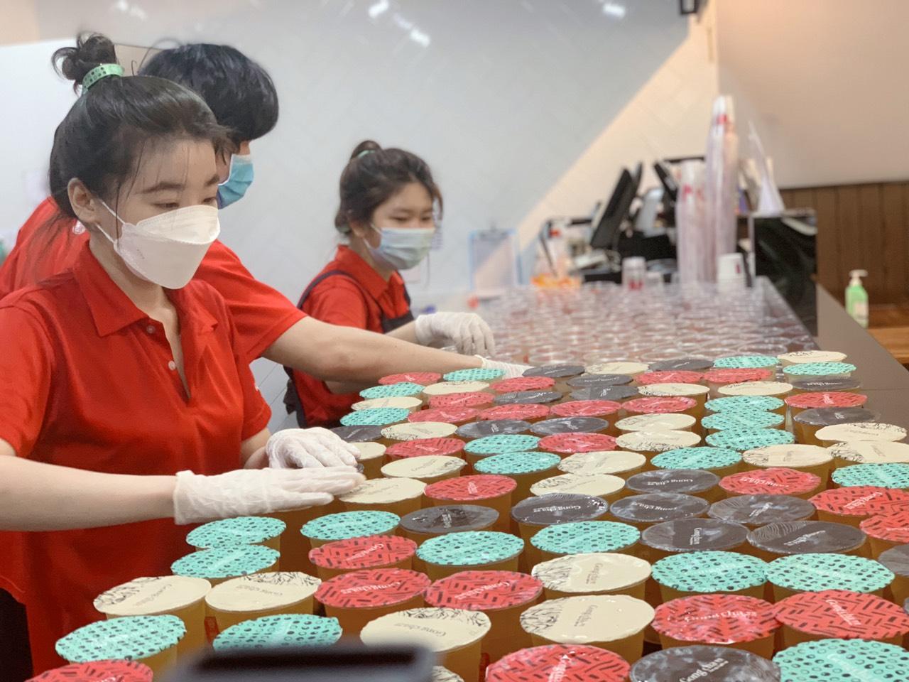 Nhân viên làm việc tại cửa hàng khi chuẩn bị trà sữa tặng lực lượng chống dịch hồi tháng 7/2021. Ảnh: Gong Cha