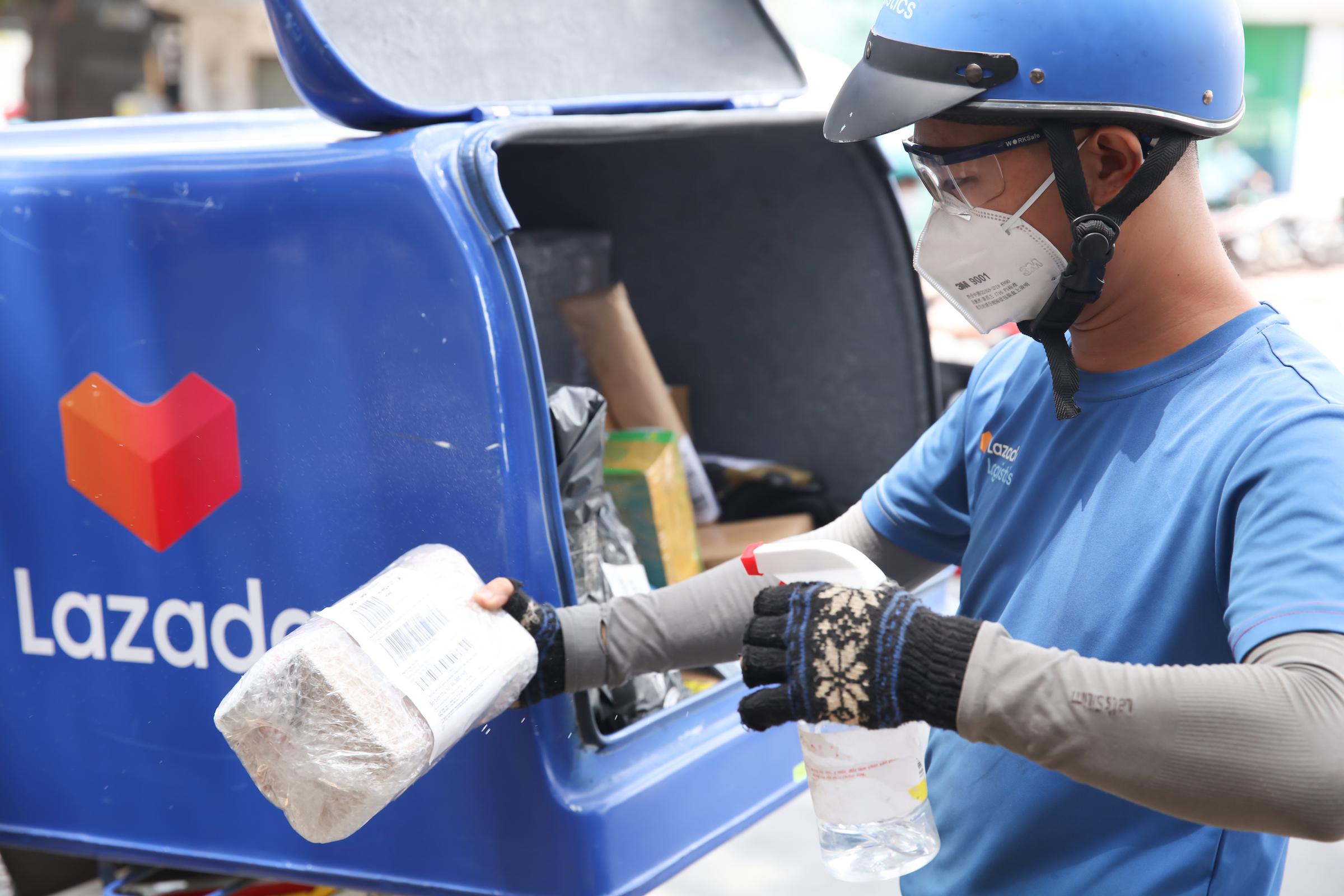 Shipper Lazada Logistics xịt khử khuẩn gói hàng trước khi giao cho người nhận. Ảnh: Lazada Việt Nam
