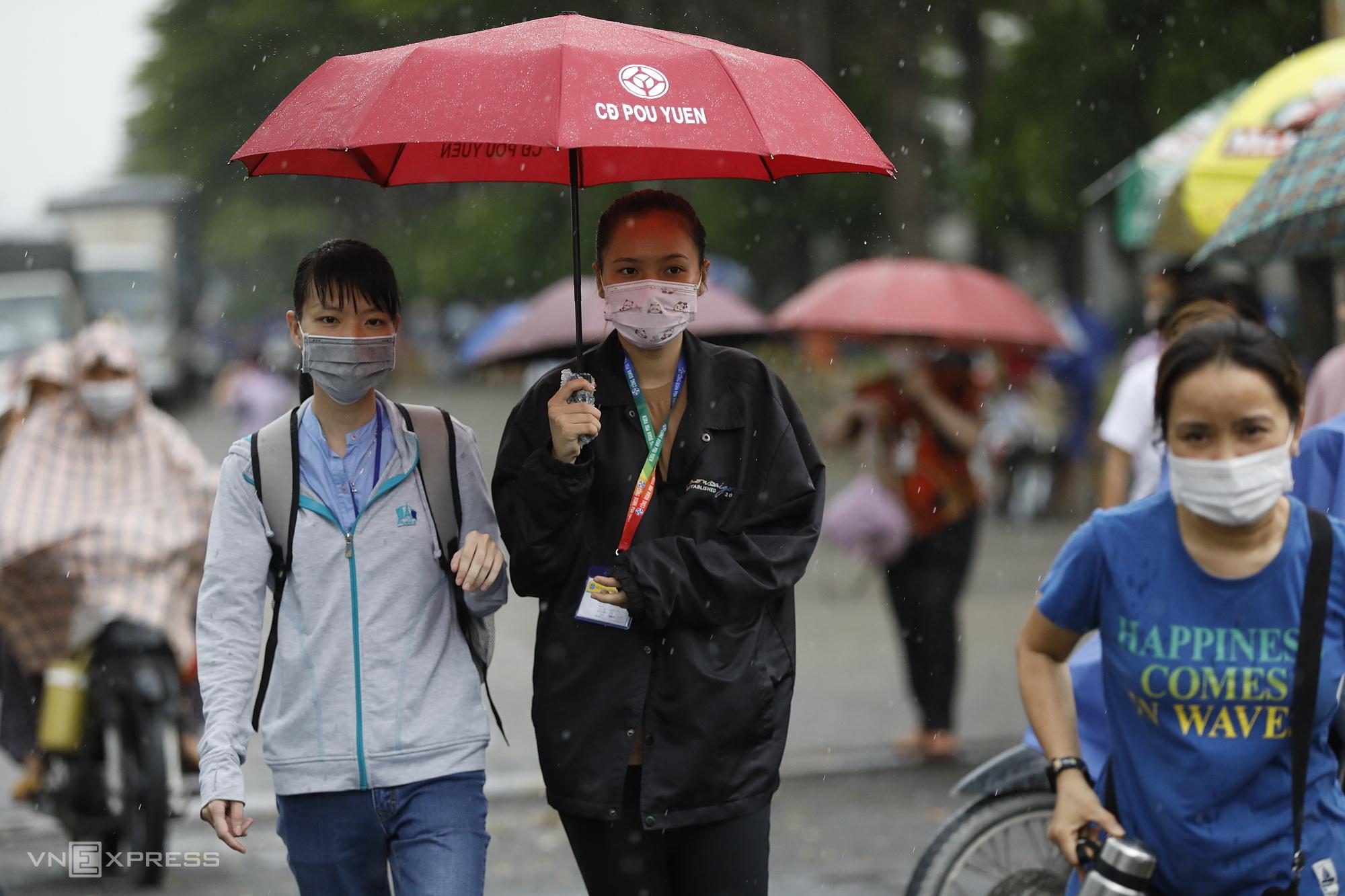 Công nhân Công ty Pouyuen ra về trong cơn mưa chiều 9/6. Ảnh: Hữu Khoa