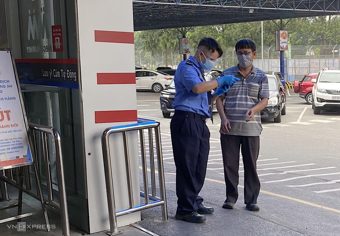 Bảo vệ một siêu thị tại phường An Phú, TP Thủ Đức đang kiểm tra thẻ vaccine của khách hàng. Ảnh: Tất Đạt