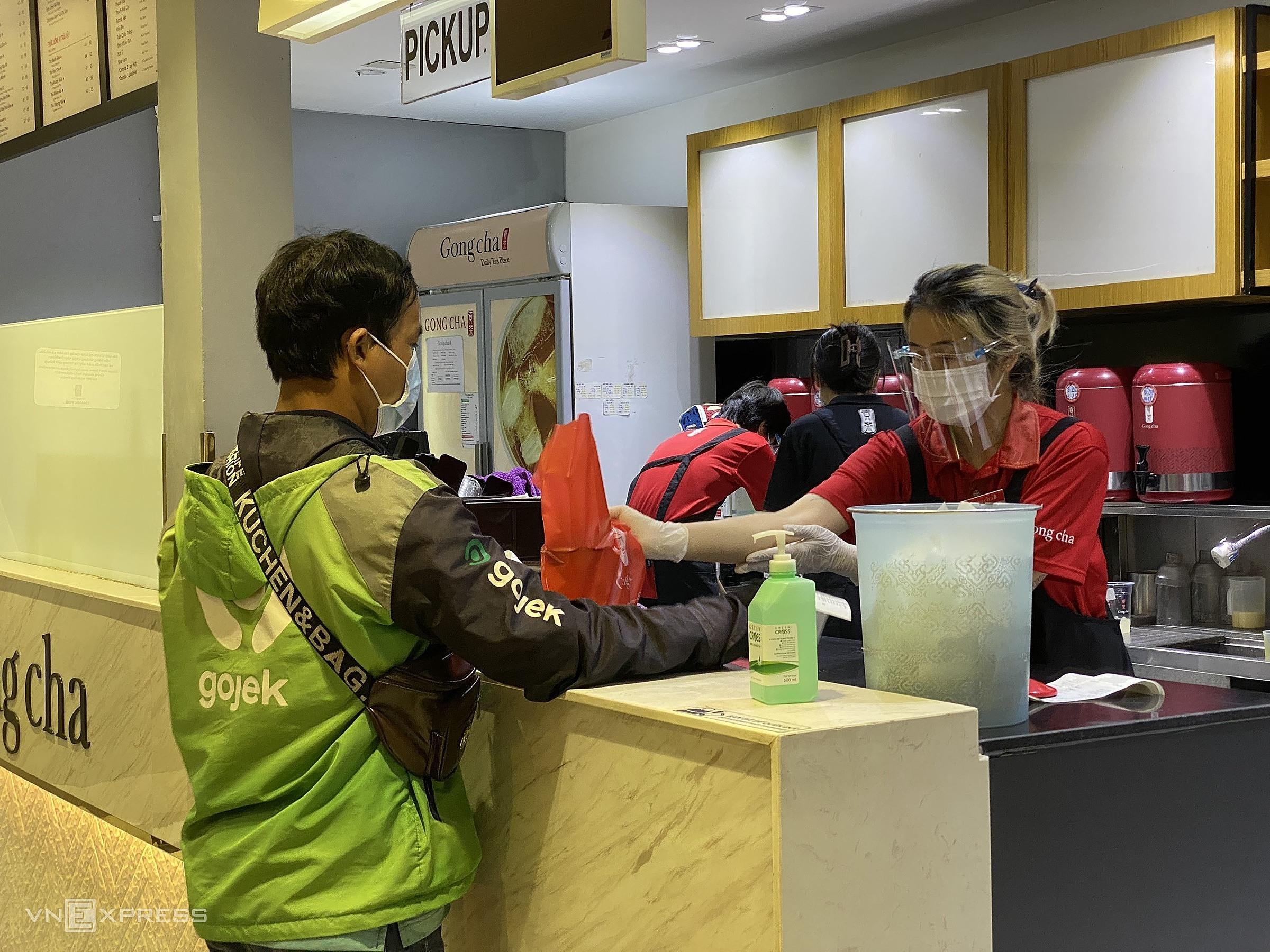 Nhân viên một cửa hàng trà sữa được trang bị bộ bảo hộ gồm khẩu trang, kính chống giọt bắn, găng tay. Ảnh: Tất Đạt