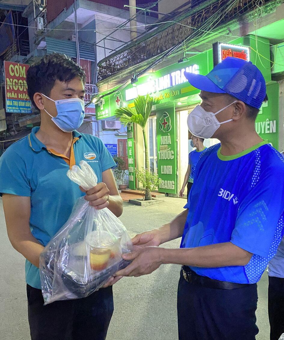 Đại diện BIDV trao cơm cho người dân Hà Nội. Ảnh: BIDV