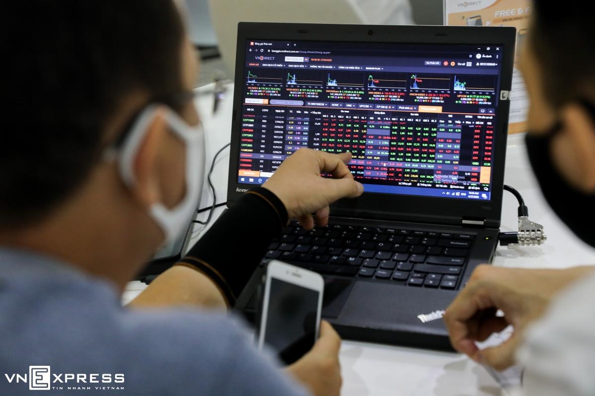 Nhà đầu tư được nhân viên công ty chứng khoán hướng dẫn xem bảng giá. Ảnh: Quỳnh Trần.
