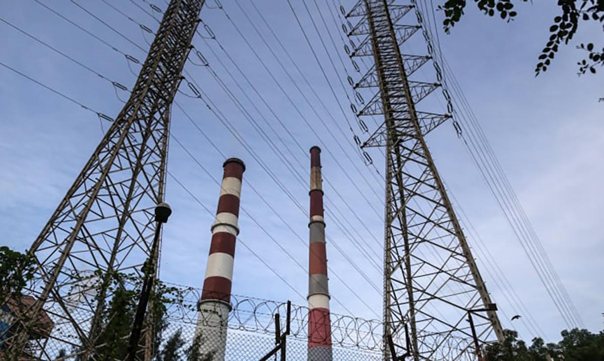 Cột điện và ống khói tại nhà máy điện Trombay Thermal của Tata Power tại Mumbai, Ấn Độ. Ảnh: Bloomberg