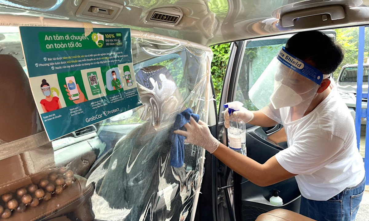 Tài xế GrabCar tại Hà Nội xịt khử khuẩn xe sáng 14/10. Ảnh công ty cung cấp.